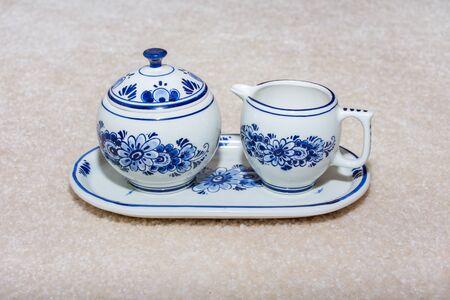 Delft Blue Cream and Sugar Porzellan Serviergeschirr auf einem Tablett. Souvenir aus Holland/Niederlande. Auf beige Hintergrund isoliert.