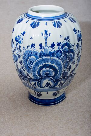 Hand made Dutch Delft Blau (blue) vase with blue designs and porcelin china on an isolated beige background. Netherlands. Banco de Imagens