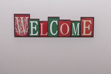 Welcome greeting sign in green and red block letters in a home with copy space.