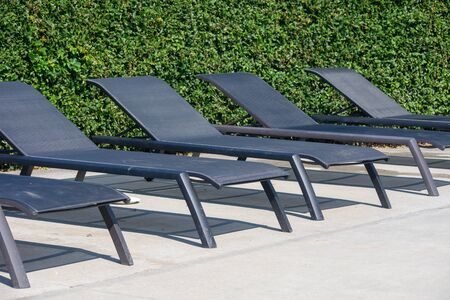 A row of empty pool chairs for lying down with a green background on a sunny day.
