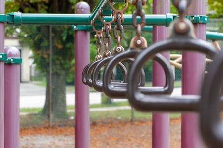 Empty monkey bars at a playground side view concept looking through rings at the goals ahead and holding on strong preventing falling and maintaining balance. Concept.
