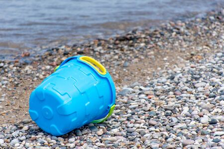 Close up of Blue bucket or pail on the seashore sitting empty in the rocky sand next to the lake with blue water in background and open concept space. Reklamní fotografie
