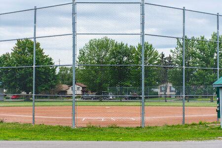 Brighton, OntarioCanada - 07222019: Baseball or softball diamond through a fence in  park in a small town Canadian city of Brighton near Pesquile Lake Provincial Park . Reklamní fotografie