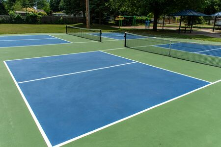 Recreational sport of pickleball court in Michigan, USA looking at an empty blue and green new court at a outdoor park.