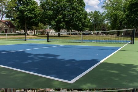 Recreational sport of pickleball court in Michigan, USA looking at an empty blue and green new court at a outdoor park. Ground View.