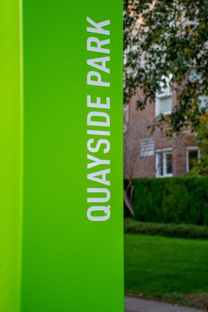 Bright Green Quayside Park sign along the New Westminster, British Columbia walkway with copy space
