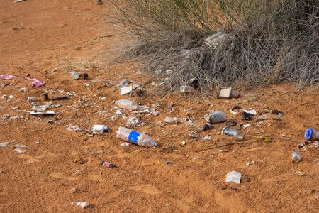 Plastic pollution in the desert sand. Need for awareness of enviornmental protection, recycling, and protecting the world. Environmental concept.