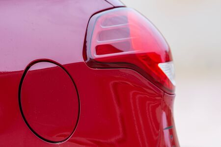 Closed gas or petrol tank and tail light for a red car for a driving, fuel, or transportation concept.