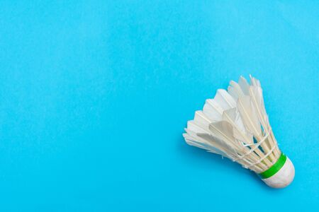 Badminton shuttlecock or birdie on a solid bright blue flat lay background symbolizing sports and activity with copy space.