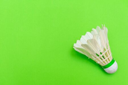 Badminton shuttlecock or birdie on a solid bright green flat lay background symbolizing sports and activity with copy space.