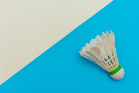 Badminton shuttlecock or birdie on a solid bright blue and white flat lay background symbolizing sports and activity with copy space.