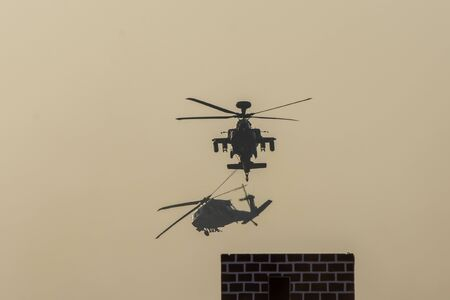 Two Military choppers in combat and war flying into the smoke and chaos and destruction. Military concept of power, force, strength, air raid. Portrait View. Stock fotó