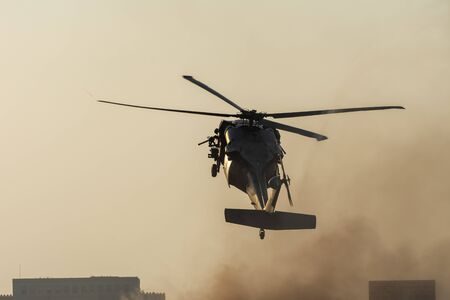 Military chopper takes off in combat and war flying into the smoke and chaos and destruction. Military concept of power, force, strength, air raid. Portrait View. Banque d'images