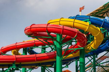 Colorful water Park twisted water slide amusement resort for luxury children and family vacations on a warm sunny tropical day.
