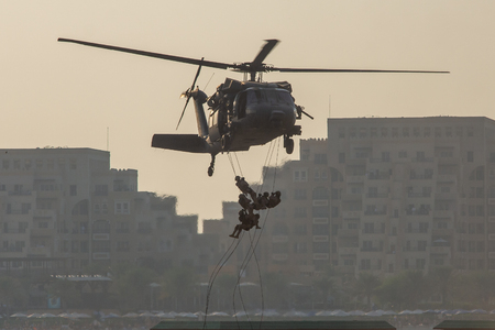 Military combat and war with helicopter flying into the chaos and destruction. Soliders suspend from rope to the ground from chopper. Military concept of power, force, strength, air raid.