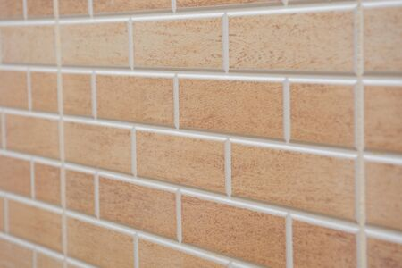 Angled view of Beige textured brick interior or exterior wall with white grout. A concept or background for interior design, construction, DIY, or building.