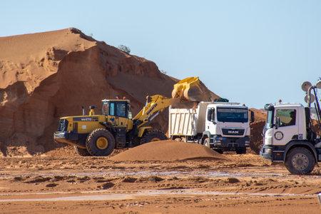 """""""Ras al Khaimah, RAK / Emiratos Árabes Unidos - 12/01/2020: Equipo de excavación de construcción de excavadoras, camiones volquete y retroexcavadoras excavan la arena para el mantenimiento de carreteras en el Medio Oriente"""""""