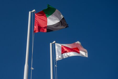 Ras al Khaimah flag (red and white) in the United Arab Emirates (UAE) north of Dubai, and  UAE flag blowing in the wind on a blue sky background.