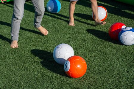 Vibrant billiards soccer/footballs balls on the green grass with children's feet kicking for recreation and fun outdoors. 免版税图像