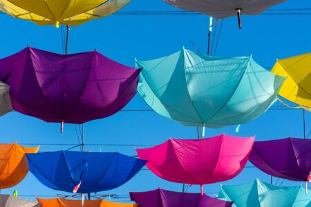 Colorful vibrant umbrellas hanging over the walking street for a festival on a blue sky sunny day.