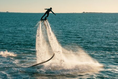 Fly boarding spinning extreme water sports in Ras al Khaimah, United Arab Emirates near Dubai at sunset having fun on the water. Recreation and sports concepts.
