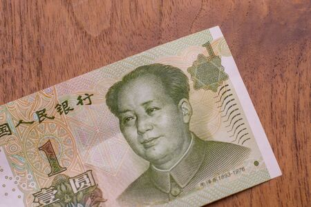 The Currency of the China - Close up of a green one remminbi or yuan note on a brown table background. Money exchange.