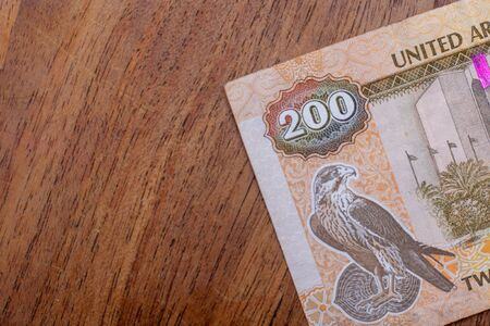 The Currency of the United Arab Emirates (UAE) - Close up of a two hundred Dirham note  on a brown table background. Money exchange.