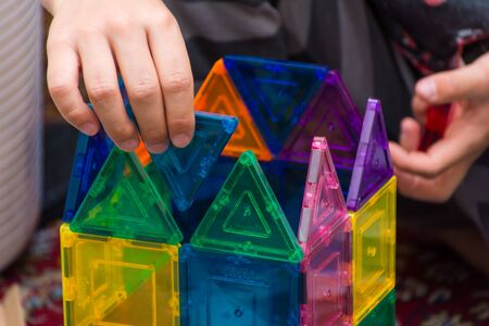 Young child building geometric magnetic shapes into a creative building at home indoors for education, problem solving, fun, enjoyment and leisure. Reklamní fotografie