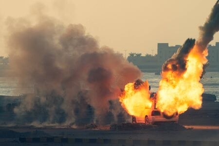 Close up of a Military strike or bomb in war on an SUV with tanks causing fire balls and explosion in the town in chaos. Military war concept. Strength, power, force, fire, explosion. 版權商用圖片