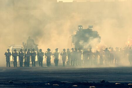 Military police riot response to a protest with tear gas, smoke, fire, explosions. Political expression, riot, protest, demostration and military concept. 版權商用圖片