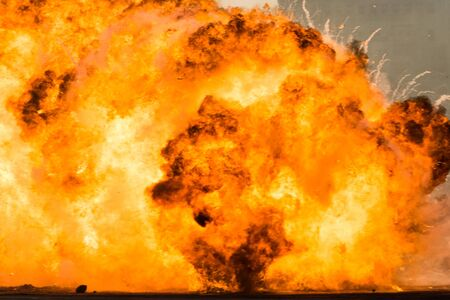 Massive orange fire explosion in military combat and war. Vehicle explosure from a tank in a city in the Middle East. Military Concept. Strength, power, explosion.