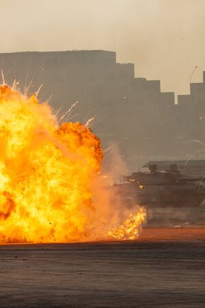 Massive fire explosion in military combat and war. Vehicle explosure from a tank in a city in the Middle East. Military Concept. Strength, power, explosion. (Portrait) 版權商用圖片