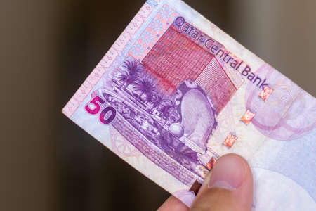 Persons hand giving the Currency of the Qatar - One fifty rial or riyal note spread out on a brown background. Money exchange.