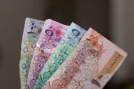 Currency of the Qatar - hundreds of rial or riyal notes spread out on a brown background. Money exchange. 版權商用圖片