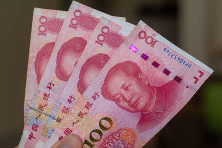 Persons hand giving the Currency of the China - One red hundred renminbi or yuan notes spread out on a brown background. Money exchange. 版權商用圖片