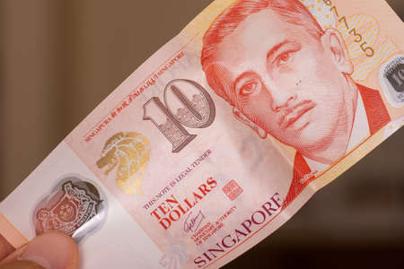 Persons hand giving the Currency of the Singapore - One red ten dollar note spread out on a brown background. Money exchange.