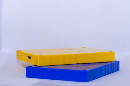 Yellow and blue portable usb hardrives stacked on isolated white background.