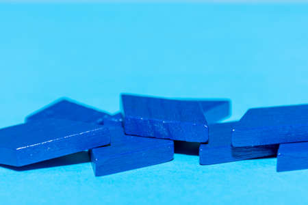 Bright colored blue tangram child geometric shape puzzle pieces  in a pile close up on blue background with copy space.