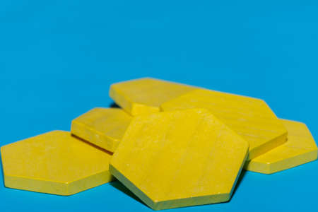 Bright colored yellow tangram child geometric shape puzzle pieces  in a pile close up on blue background with copy space.