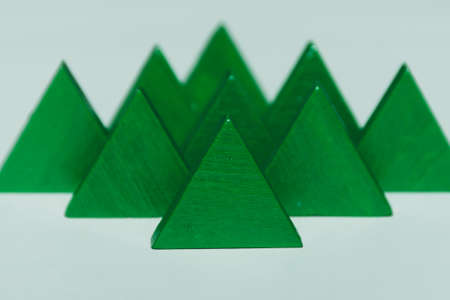 Bright green triangle tree like tangram pieces lined up on soft green background. Child's toy's and play concepts. 写真素材