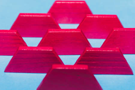 Bright pink tangram geometric shapes lined up on bright blue background in a row. Child's toys and problem solving concepts.