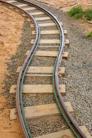 Twisted Railway track at an amusement park symbolizing moving ahead in business and life, travel and train concepts.