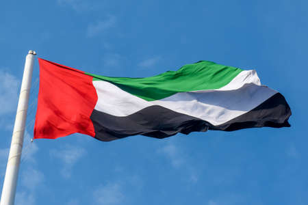 United  Arab Emirates Flag flying and waving in the sunshine with a deep blue sky background.
