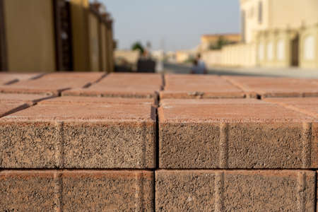 Red bricks laid out in a row for masonry, contruction and development concepts with residential area defocused in background.