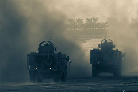 Military chopper and army vehicles flying and driving entering into the smoke and war . Military concept of power, force, strength, air raid, explosion.