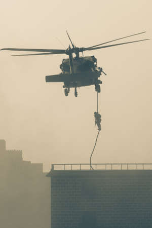 Military combat and war with helicopter flying into the chaos and destruction. Soliders suspend from rope to the ground from chopper. Military concept of power, force, strength, air raid. Portrait View. 免版税图像
