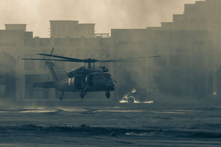 Military combat and war with helicopter landing in the chaos and destruction. Smoke and fire on the ground. Military concept of power, force, strength, air raid. 스톡 콘텐츠