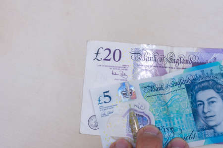Persons hand giving the Currency of the England in the United Kingdom - One purple twenty pound and blue five pound note spread out on a white background. Money exchange.