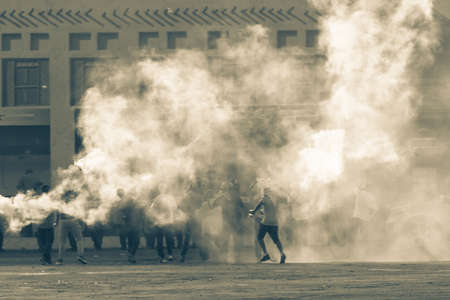Military police riot response to a protest with tear gas, smoke, fire, explosions. Political expression, riot, protest, demostration and military concept. 免版税图像