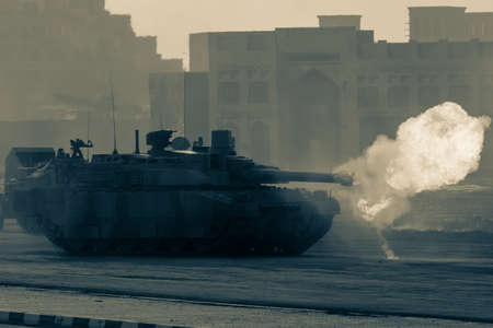 Military explosion, fighting, war and chaos. Tanks driving by through the smoke and destruction. Military concept.